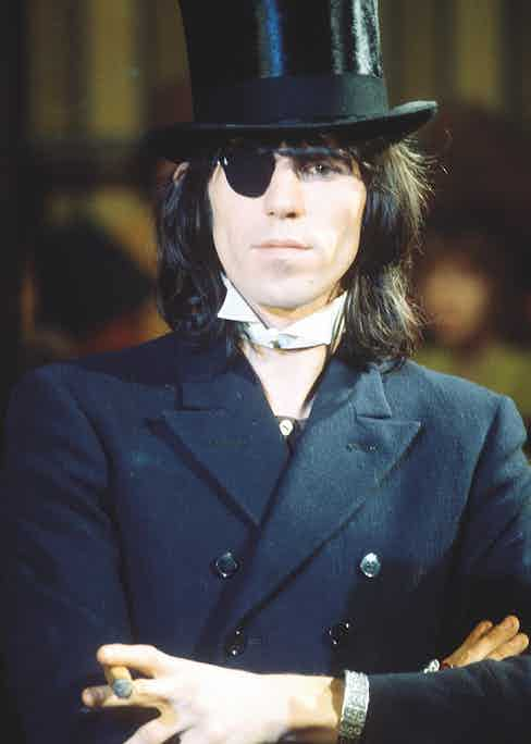 Performing at The Rolling Stones Rock and Roll Circus wearing a double-breasted peaked lapel jacket, detachable wing-tip collar, eye-patch and top hat, 1968. Photograph by REX/Shutterstock.
