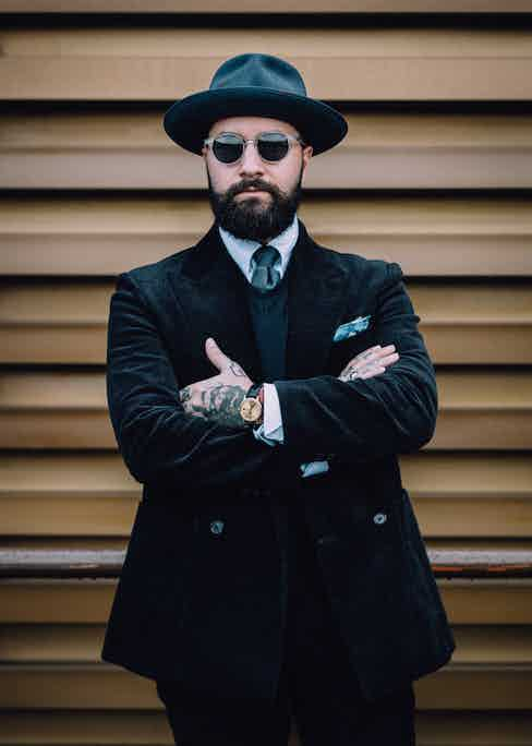 Jared Acquaro demonstrating the art of tonal simplicity with a peaked lapel, double-breasted black corduroy suit and matching trilby hat at Pitti Uomo 93. Photograph by Jamie Ferguson.