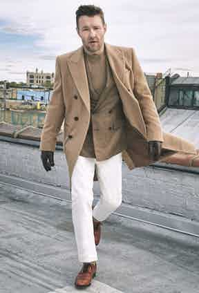 Joel Edgerton displays a monochromatic aesthetic in a camelhair double-breasted overcoat, chocolate brown napa leather gloves, all Gieves & Hawkes; biscuit-brown cashmere double-breasted jacket, Thom Sweeney; caramel cashmere jumper, Cerruti 1881; tan brown, calf leather Balmoral shoes, John Lobb; gold with brown silk, paisley pocket-handkerchief, Dunhill; beige cotton socks, Pantherella. Photograph by Gavin Bond.