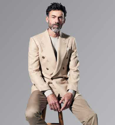A subtle tonal uniform of a cream cashmere and camelhair double-breasted jacket, Chester Barrie for The Rake; oatmeal Merino wool sweater, John Smedley; khaki cotton trousers, Gieves & Hawkes; red and white paisley linen pocket-square, Calabrese Napoli for The Rake. Photograph by Jake Walters.