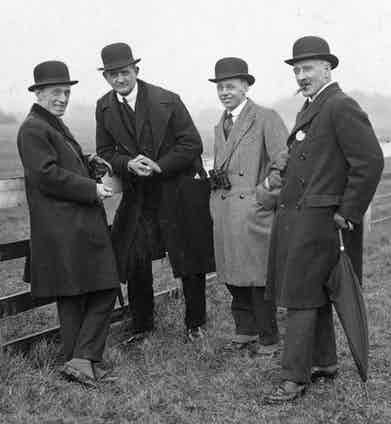 Spectators at the Cheltenham Steeplechases wear an array of double-breasted overcoats, suits, club collar shirts and bowler hats. Photograph by Topical Press Agency/Getty Images.