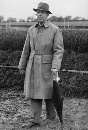Lord Willoughby De Broke wears a belted raincoat with turn up trousers and a fedora hat at Cheltenham Races, 1951. Photograph by ANL/REX/Shutterstock.