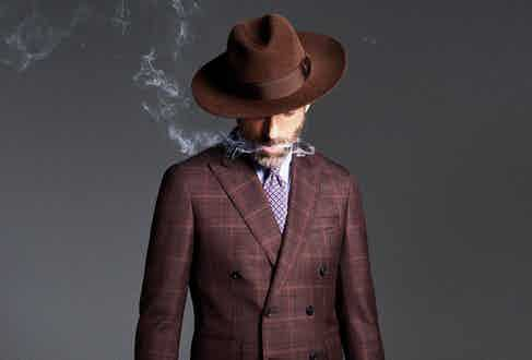 Brown wool Prince of Wales check, double-breasted jacket, Gieves & Hawkes; white and blue stripe cotton shirt, Caruso; blue and red floral foulard unlined silk tie, Francesco Marino at The Rake; chocolate brown felt Louisiana fedora, Lock Hatters.