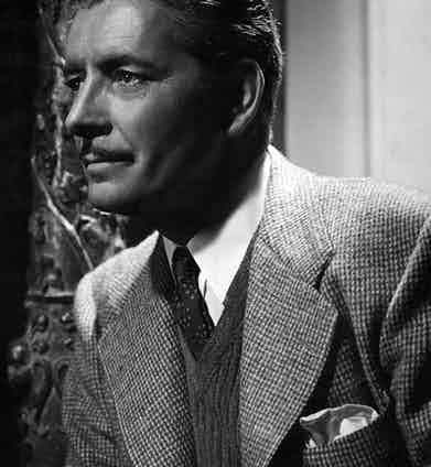 Ronald Colman wears a V-neck sweater underneath tailoring in The Talk of the Town, 1942.