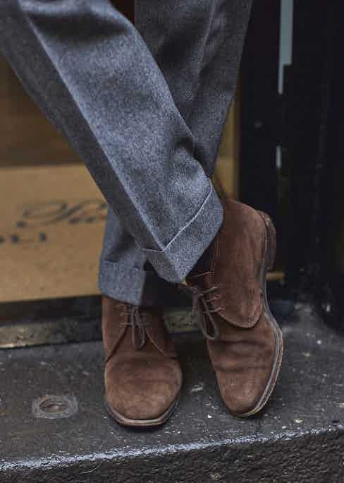 With his grey flannel suit he spots a pair of chukka boots.