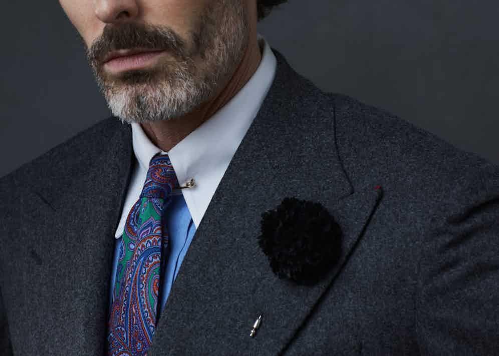 Black silk flower lapel pin, Cinabre; charcoal grey wool suit, Dalcuore; blue pin collar shirt, Edward Sexton; paisley print silk tie, Sera Fine Silk. Styling by Jo Grzeszczuk, photograph by Olivier Barjolle.