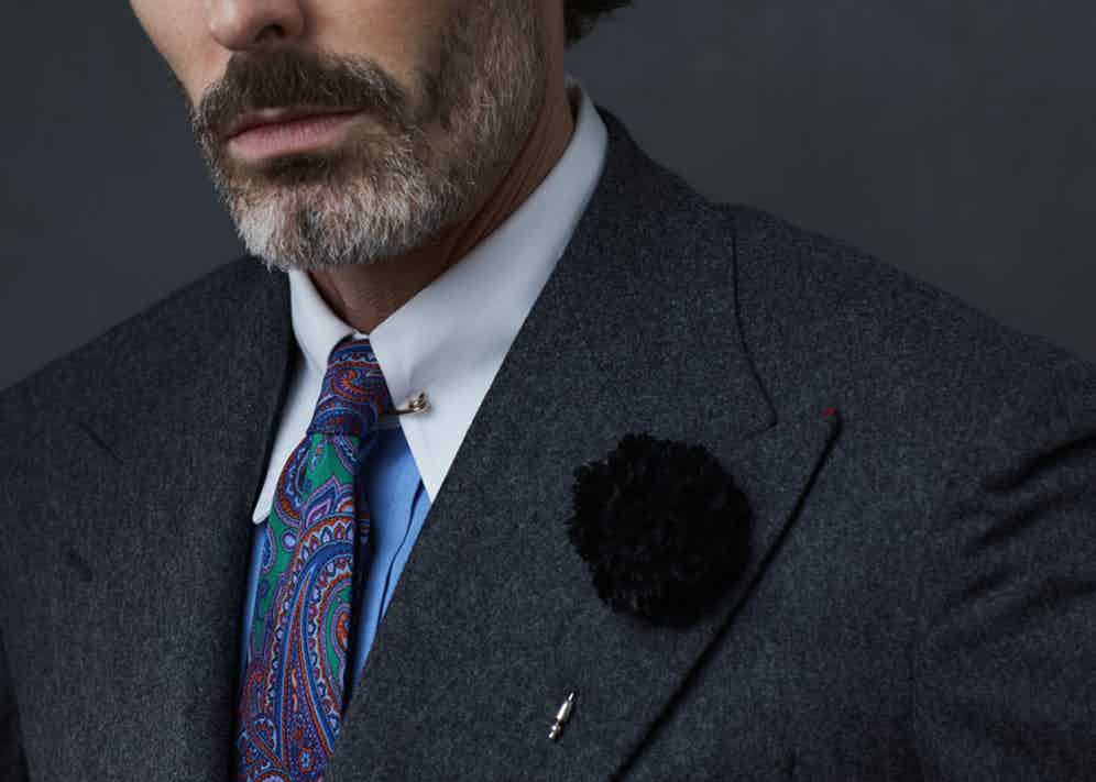 Black silk flower lapel pin, Cinabre; charcoal grey wool suit, Dalcuore; blue pin collar shirt, Edward Sexton; paisley print silk tie, Sera Fine Silk. Styling by Jo Grzeszczuk, photograph by Olivier Barjolle.