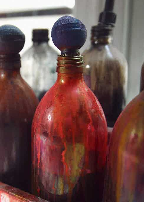 A variety of coloured dye sitting in glass containers in the Cinabre workshop.