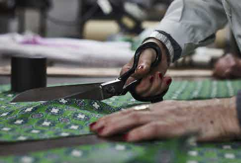 A craftswoman carefully cuts Francesco Marino's printed silk cloth. Photograph by James Munro.