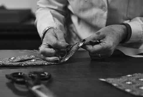 A craftswoman closes the blade with a single thread. Photograph by James Munro.
