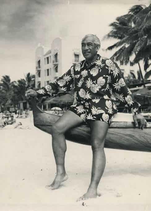Surfing legend Duke Kahanamoku wears a long sleeve pineapple motif Hawaiian shirt with matching shorts on a beach in Hawaii, circa 1945.