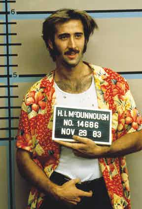 Nicolas Cage demonstrates a casual approach wearing his shirt open with a white vest shirt underneath in Raising Arizona, 1987. Photograph by Moviestore/REX/Shutterstock