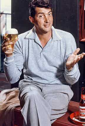 Dean Martin, a key player in The Rat Pack, raises a glass wearing a wide-collared, long-sleeve grey polo shirt.