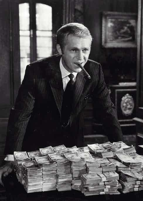 McQueen wearing a sharp pinstripe suit with a contrasting polka dot pocket square in The Thomas Crown Affair, 1968.