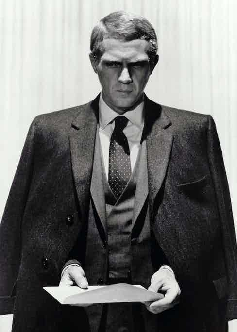 Looking sharp in The Thomas Crown Affair, 1968, wearing a three-piece suit with a double-breasted waistcoat, paired with a white spread collar shirt and polka dot tie.