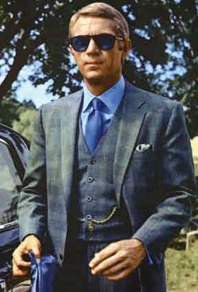 Throughout The Thomas Crown Affair, 1968, McQueen is exceptionally well dressed. This grey Prince of Wales check with hints of blue was created by the famed Savile Row tailor, Douglas Hayward.