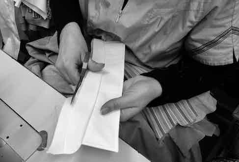An artisan cutting the collar of an Ign. Joseph shirt.