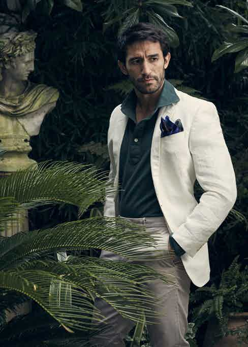 White linen jacket, Richard James; forest green long sleeve cotton polo shirt, Luca Avitabile; blue and green paisley silk pocket square, New & Lingwood. Styling by Jo Grzeszczuk, photograph by Olivier Barjolle.