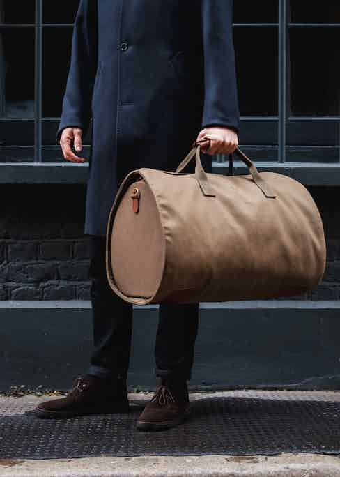 The olive version of the suit carrier holdall provides a nice contrast to a dark casual outfit.