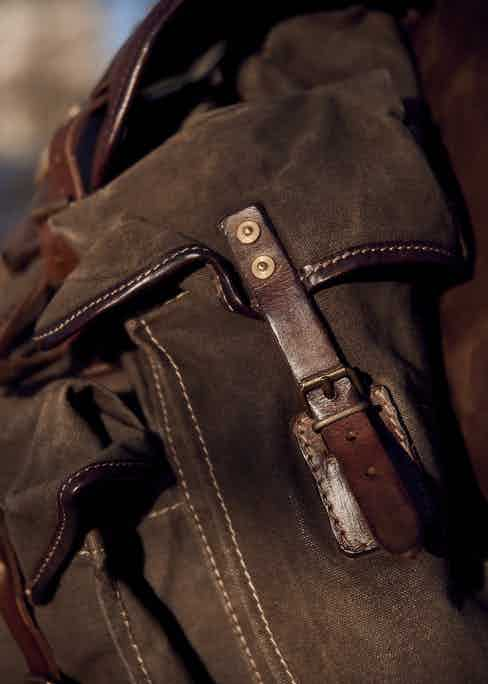There are two cowhide leather flap pockets that are fastened with brass buckles.
