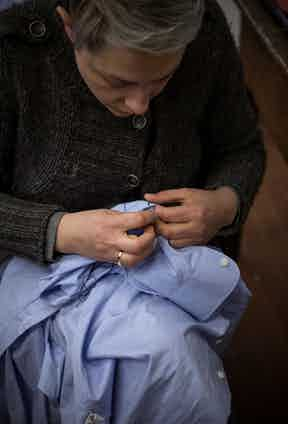 A blue cotton shirt being meticulously finished.