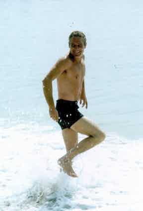 Paul Newman dons a pair of short black swimming trunks while running in the surf, 1968.