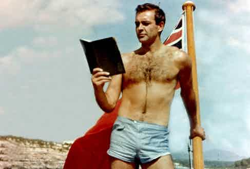 Sean Connery takes time out from filming Thunderball while wearing short pale blue swimming trunks featuring a small pocket on the front, 1965.