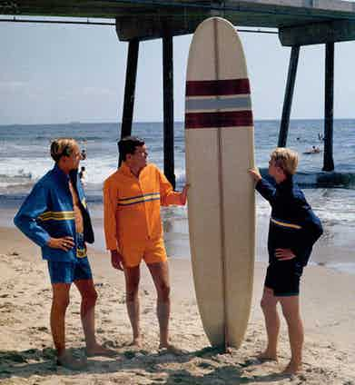Captured by LeRoy Grannis donning matching swim shorts and zip-up jackets, a group of American surfers pose with a surf board on Sunset Beach, circa 1965.