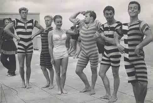 A group of men showcase striped all-in-one Victorian swimsuits, circa 1940.