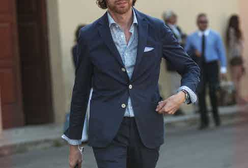 A tonal ensemble demonstrated at Pitti Uomo which pairs a blue floral shirt with a navy single-breasted suit. Photograph by Guerrisms.