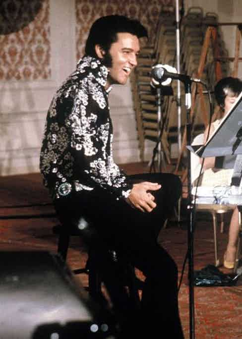 Elvis Presley sports a black shirt with a white floral motif along with his signature quiff and side-burns while rehearsing at the International Hotel Las Vegas, 1970.
