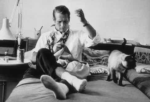 Paul Newman adorns his neck with a floral printed neck scarf while sewing his jacket and hanging out with photographer Sanford Roth's cat Louis XIV, circa 1959.