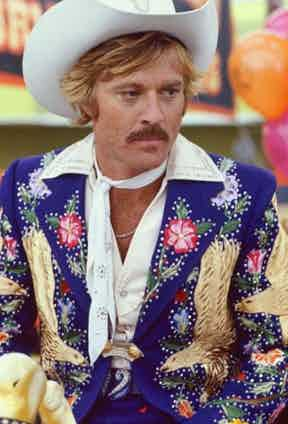 Robert Redford wears a brightly coloured Western-style jacket embroidered with floral motifs and eagles with a white neck scarf and white cowboy hat in The Electric Horseman, 1979.