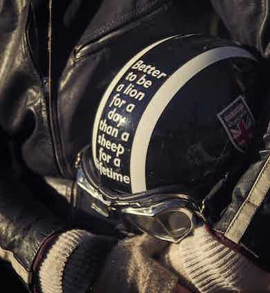 Edie's helmet sports a quote to live by. She also wears a vintage black leather one-piece motorcycle suit that Nick sourced for her.