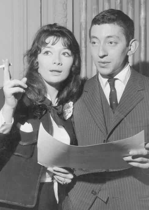 Gainsbourg's early style was more formal, pictured here wearing a pinstripe three-piece suit with notched lapels and spotted tie with actress and singer Juliette Greco in Paris, 1959. Photograph by Archive Photos/Getty Images.