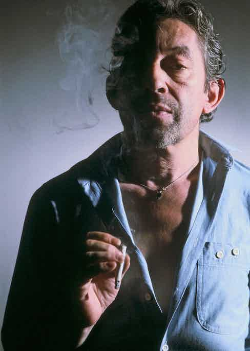 Opting for a casual denim shirt worn open and a silver necklace, Gainsbourg stands in his signature pose, cigarette in hand in Paris, 1985. Photograph by Jean-Jacques BERNIER/Gamma-Rapho via Getty Images.