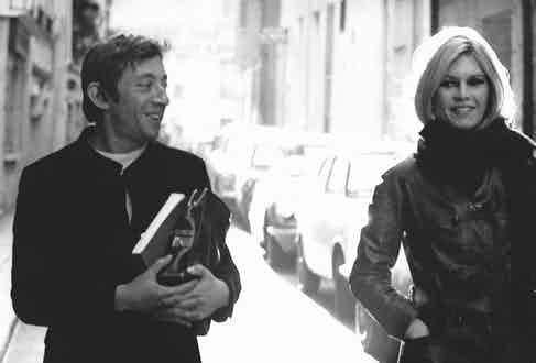 Simple and refined in a collarless jacket with a white round-neck shirt underneath, Gainsbourg walks with then-girlfriend Brigitte Bardot in Paris, 1960. Photograph by REPORTERS ASSOCIES/Gamma-Rapho via Getty Images.
