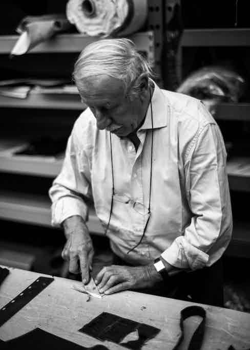 A craftsman trims precise pieces of leather at a factory in Italy.