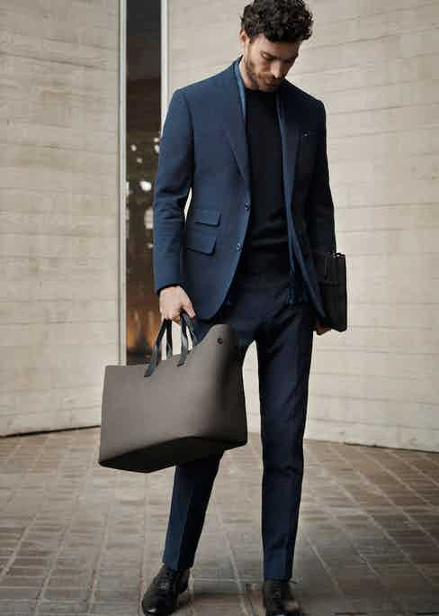 Sleek and sophisticated, the technical canvas tote bag features leather straps, button-fastened sides and internal zip pockets.