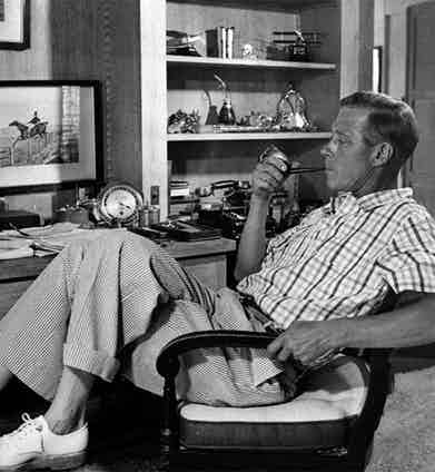 The Duke of Windsor relaxes and has a smoke in a pair of seersucker trousers with a turn-up, worn sans socks with a pair of white derbies.