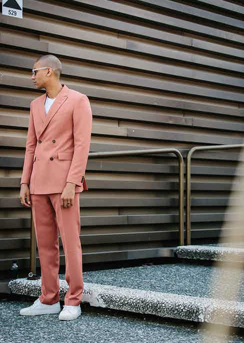 Downplay the flamboyance of a pastel pink suit with a pair of fresh white sneakers and matching t-shirt.
