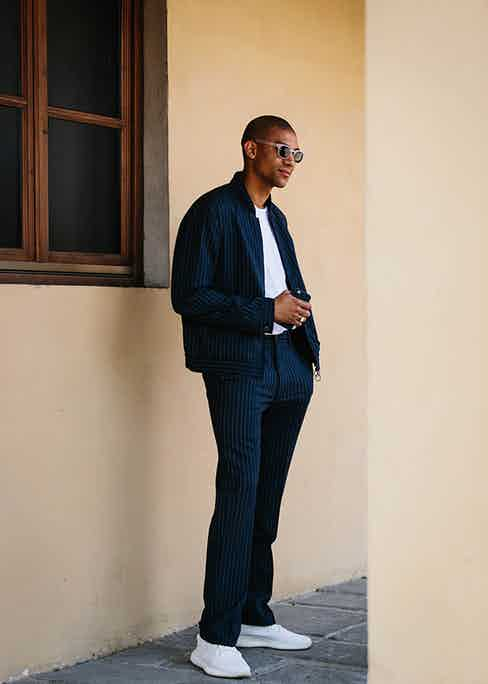 Pinstripes can be consummately casual when matched up with a minimal pair of white sneakers.