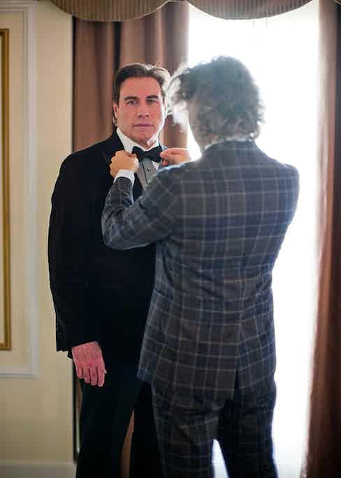 Designer Matteo Perin puts the final touches to John Travolta's black tie ensemble (Thorsten Overgaard).