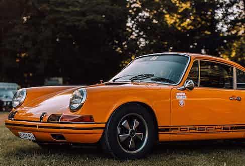 An orange Porsche 911 with racing decals.