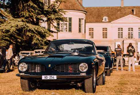 A classic Ferrari with round headlights at the Concours d'Elégance.