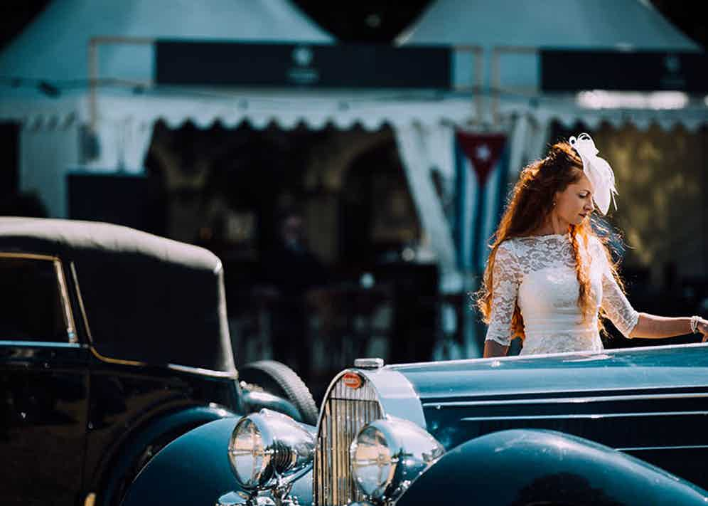 A woman in a lace dress examines a vintage Bugatti.