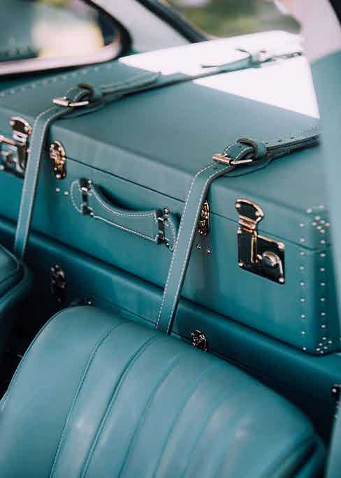 The sleek, monochromatic blue interior of a classic car with luxury matching luggage from Globe Trotter.
