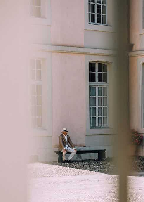 A well-dressed gentleman relaxes at the picturesque setting for the Concours d'Elégance Suisse.