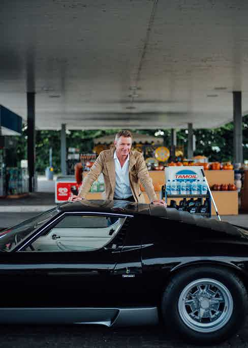 Simon wears a brown jacket with a blue shirt whilst filling up a classic glossy black car.