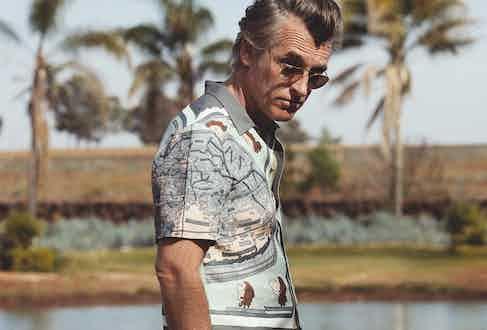 Multicolour silk printed short sleeve shirt, Santoni Edited by Marco Zanini; grey silk trousers, Ermenegildo Zegna Couture; yellow gold, hexagonal frame aviators with pink lenses, Ray-Ban.